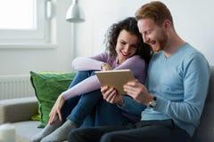 Νέο ζεύγος που χρησιμοποιεί την ψηφιακή ταμπλέτα στο σπίτι Στοκ Εικόνες