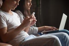 Νέο ζεύγος που χρησιμοποιεί τις συσκευές που δεν έχουν καμία επικοινωνία μεταξύ στοκ φωτογραφία με δικαίωμα ελεύθερης χρήσης