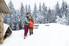 Νέο ζεύγος που χρησιμοποιεί το έξυπνο τηλεφωνικό χιονώδες χωριό ξύλινοι άνδρας και γυναίκα εξοχικών σπιτιών σε απευθείας σύνδεση  Στοκ εικόνα με δικαίωμα ελεύθερης χρήσης