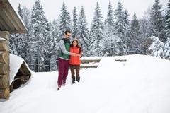 Νέο ζεύγος που χρησιμοποιεί το έξυπνο τηλεφωνικό χιονώδες χωριό ξύλινοι άνδρας και γυναίκα εξοχικών σπιτιών σε απευθείας σύνδεση  Στοκ φωτογραφία με δικαίωμα ελεύθερης χρήσης