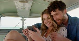Νέο ζεύγος που χρησιμοποιεί το κινητό τηλέφωνο 4k απόθεμα βίντεο