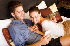 Νέο ζεύγος που χρησιμοποιεί το τηλέφωνο σε ένα ασιατικό δωμάτιο ξενοδοχείου Στοκ εικόνα με δικαίωμα ελεύθερης χρήσης