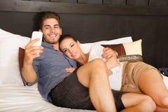 Νέο ζεύγος που χρησιμοποιεί το τηλέφωνο σε ένα ασιατικό δωμάτιο ξενοδοχείου Στοκ Φωτογραφία