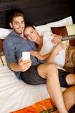 Νέο ζεύγος που χρησιμοποιεί το τηλέφωνο σε ένα ασιατικό δωμάτιο ξενοδοχείου Στοκ Εικόνες