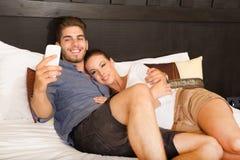 Νέο ζεύγος που χρησιμοποιεί το τηλέφωνο σε ένα ασιατικό δωμάτιο ξενοδοχείου Στοκ Φωτογραφίες