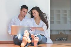Νέο ζεύγος που χρησιμοποιεί το lap-top στο σπίτι Στοκ φωτογραφίες με δικαίωμα ελεύθερης χρήσης