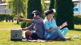 Νέο ζεύγος που χρησιμοποιεί vr τα γυαλιά στο πάρκο φιλμ μικρού μήκους