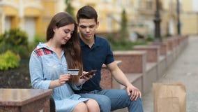 Νέο ζεύγος που ψωνίζει on-line με την πιστωτική κάρτα απόθεμα βίντεο