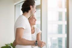Νέο ζεύγος, σε ένα σύγχρονο επίπεδο, που κρατά βασικός στοκ φωτογραφίες