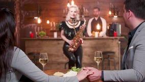 Νέο ζεύγος σε μια επιδοκιμασία ημερομηνίας σε ένα θηλυκό saxophonist απόθεμα βίντεο