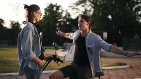 Νέο ζεύγος στα ίδια μπλε πουκάμισα hng έξω στην οδό Το αγόρι κάθεται σε ένα ηλεκτρο ποδήλατο, και μια συζήτηση σε δικοί του απόθεμα βίντεο