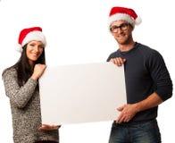 Νέο ζεύγος στα καπέλα santa που κρατά τον κενό πίνακα για τη διαφήμιση Στοκ Φωτογραφία