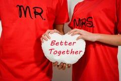 Νέο ζεύγος στα κόκκινα πουκάμισα που κρατά την άσπρη καρδιά υφάσματος με το κείμενο Στοκ εικόνες με δικαίωμα ελεύθερης χρήσης