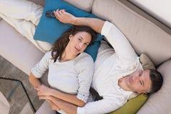 Νέο ζεύγος στην τηλεοπτική τοπ άποψη προσοχής καναπέδων Στοκ φωτογραφία με δικαίωμα ελεύθερης χρήσης