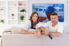 Νέο ζεύγος στην τηλεόραση προσοχής καναπέδων Στοκ Εικόνες