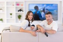 Νέο ζεύγος στην τηλεόραση προσοχής καναπέδων Στοκ εικόνα με δικαίωμα ελεύθερης χρήσης