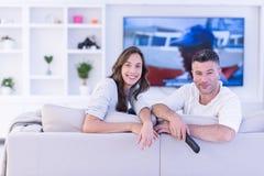 Νέο ζεύγος στην τηλεόραση προσοχής καναπέδων Στοκ εικόνες με δικαίωμα ελεύθερης χρήσης
