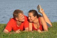 Νέο ζεύγος στη χλόη στην παραλία στο καλοκαίρι στοκ φωτογραφίες
