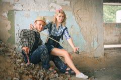 Νέο ζεύγος στις φόρμες με τα εργαλεία Έννοια της επισκευής κατασκευής και σπιτιών Στοκ φωτογραφία με δικαίωμα ελεύθερης χρήσης