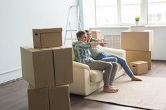 Νέο ζεύγος στον καναπέ που κινείται στο καινούργιο σπίτι Στοκ Φωτογραφίες