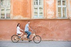 Νέο ζεύγος στο αναδρομικό διαδοχικό ποδήλατο στην πόλη οδών στοκ φωτογραφίες