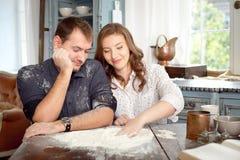 Νέο ζεύγος στο παιχνίδι κουζινών με το αλεύρι Αστείες στιγμές, χαμόγελα, μαγείρεμα, ευτυχές μαζί, μνήμες Στοκ εικόνα με δικαίωμα ελεύθερης χρήσης