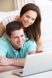 Νέο ζεύγος στο φορητό προσωπικό υπολογιστή Στοκ Φωτογραφία