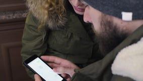 Νέο ζεύγος τουριστών που φαίνεται χάρτης στο τηλέφωνο app κυττάρων στον καφέ απόθεμα βίντεο