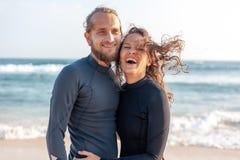 Νέο ζεύγος των ευτυχών surfers χαμόγελου στην ωκεάνια ακτή, έννοια ταξιδιού αθλητικών διακοπών στοκ εικόνες