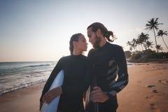 Νέο ζεύγος των ευτυχών surfers χαμόγελου στην ωκεάνια ακτή, έννοια ταξιδιού αθλητικών διακοπών στοκ φωτογραφία