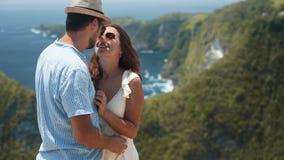 Νέο ζεύγος των newlyweds που αγκαλιάζει, φλερτάροντας, ωκεάνια άποψη σχετικά με το υπόβαθρο, σε αργή κίνηση φιλμ μικρού μήκους
