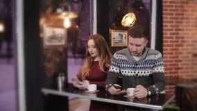 Νέο ζεύγος χρησιμοποιώντας και κοιτάζοντας επίμονα στο smartphone καθμένος στον καφέ φιλμ μικρού μήκους