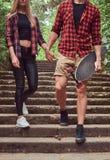 Νέο ζεύγος hipster, περίπατος σε ένα πάρκο, που κρατά τα χέρια, που κατεβαίνουν τα σκαλοπάτια Στοκ εικόνες με δικαίωμα ελεύθερης χρήσης