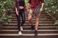 Νέο ζεύγος hipster, περίπατος σε ένα πάρκο, που κρατά τα χέρια, που κατεβαίνουν τα σκαλοπάτια Στοκ Εικόνα