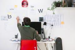 Νέο δημιουργικό άτομο σχεδιαστών που εργάζεται στο γραφείο. Στοκ Εικόνες