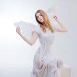 Νέο, θαυμάσιο ξανθό κορίτσι στην εικόνα ενός αγγέλου με τα άσπρα φτερά Στοκ Εικόνες