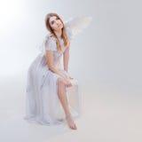 Νέο, θαυμάσιο ξανθό κορίτσι στην εικόνα ενός αγγέλου με τα άσπρα φτερά Στοκ Φωτογραφία