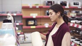 Νέο θηλυκό κοστούμι που επιλέγει τη νέα ηλεκτρική κατσαρόλα στο κατάστημα συσκευών που συγκρίνει τα διαφορετικά πρότυπα στη σειρά απόθεμα βίντεο