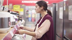 Νέο θηλυκό κοστούμι που επιλέγει τη electical αργός-κουζίνα από ποικίλο σκεύος για την κουζίνα σε ένα κατάστημα συσκευών απόθεμα βίντεο