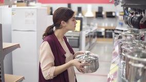 Νέο θηλυκό κοστούμι που επιλέγει το δοχείο μαγείρων από ποικίλο σκεύος για την κουζίνα σε ένα κατάστημα συσκευών Να εξετάσει προσ φιλμ μικρού μήκους