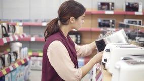 Νέο θηλυκό κοστούμι που επιλέγει το νέο toster στο κατάστημα συσκευών Έρευνα του σκεύους για την κουζίνα απόθεμα βίντεο