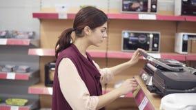 Νέο θηλυκό κοστούμι που ψάχνει το σκεύος για την κουζίνα στο κατάστημα συσκευών Εξέταση των τηγανίζοντας τηγανιών χάλυβα Ξεφύλλισ απόθεμα βίντεο