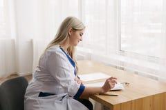 Νέο θηλυκό λειτουργώντας γραφείο γιατρών στο γράψιμο δωματίων γιατρών ` s Στοκ Εικόνα