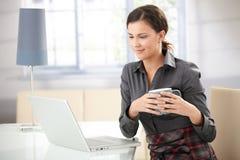Νέο θηλυκό περιοδεύοντας Διαδίκτυο που χαμογελά στο σπίτι στοκ εικόνα με δικαίωμα ελεύθερης χρήσης