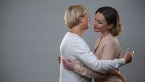Νέο θηλυκό που αγκαλιάζει την ηλικιωμένη μητέρα στο γκρίζο υπόβαθρο, ο φιλμ μικρού μήκους