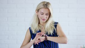 Νέο θηλυκό που εξετάζει το wristwatch φιλμ μικρού μήκους
