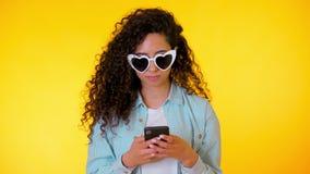 Νέο θηλυκό που χαμογελά και που χρησιμοποιεί το κινητό τηλέφωνο πέρα από το κίτρινο υπόβαθρο Όμορφη μικτή εκμετάλλευση κοριτσιών  απόθεμα βίντεο