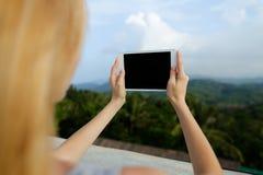 Νέο θηλυκό πρόσωπο χρησιμοποιώντας την ταμπλέτα και παίρνοντας τις φωτογραφίες στο υπόβαθρο βουνών στοκ εικόνες