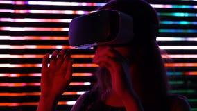 Νέο θηλυκό στην κάσκα εικονικής πραγματικότητας, σύγχρονη ψυχαγωγία, υπόλοιπο πόλεων νύχτας απόθεμα βίντεο