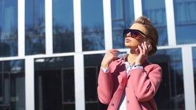 Νέο θηλυκό στο μοντέρνο παλτό που εξηγεί κάτι στο έξυπνο τηλέφωνο απόθεμα βίντεο